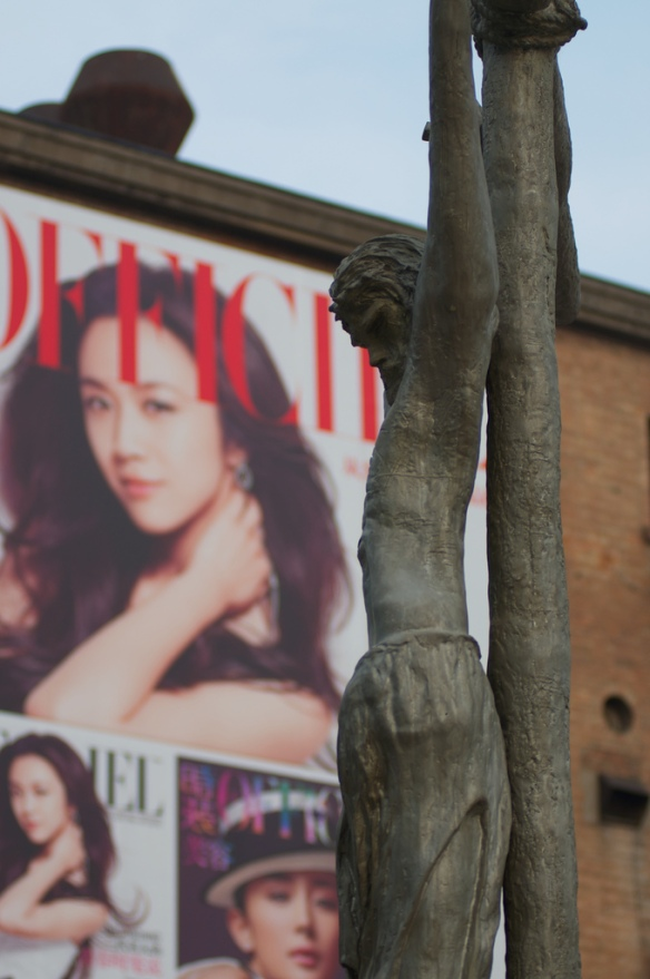 This statue was in the 798 art district in Beijing, which was ironic enough.  The billboard on the walls just layered on top...